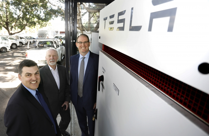 Three men in front of Tesla machine