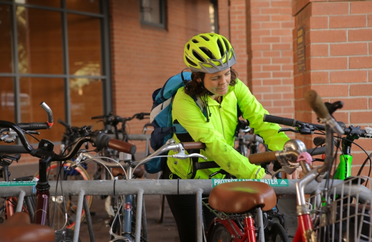 Women locking her bike to a bike rack